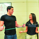 Athletic Trainer works with UCF student on resistant strength.