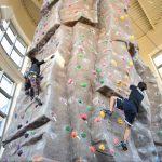 students rock climbing indoors at the Climbing Tower