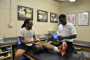 UCF RWC Athletic Trainer attends to a student at the Athletic Training clinic.