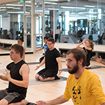 Students taking yoga at the Group Exercise Studio at RWC@Downtown.