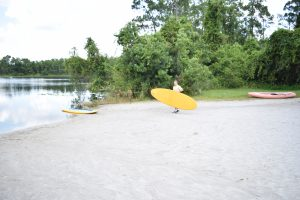 Student carrying a paddleboard at Lake Claire