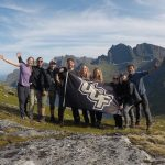 Students holding UCF flag on top of a mountain