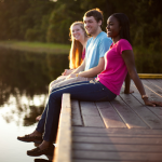Students sitting on the dock at Lake Claire