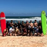 diverse group of students at the beach for a surfing trip
